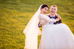 Portrait of cheerful bridegroom carrying bride on grassy field Stock Photography