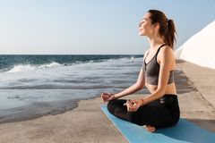 Portrait of cheerful brunette in sportwear sitting in lotos pose. While practicing meditation at seaside Stock Image