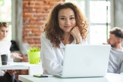 Portrait of cheerful business African-American lady working on laptop. stock photo