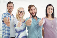 Portrait of cheerful business people with thumbs up Stock Photo