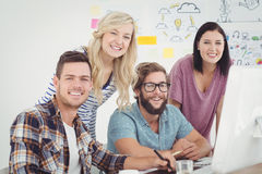 Portrait of cheerful  business professionals working at computer desk Stock Photos