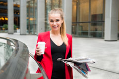 Portrait of cheerful business woman holding coffee and newspaper and enjoying her brake out of office building Royalty Free Stock Images
