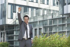 Portrait of cheerful businessman with arm raised standing outside office building Royalty Free Stock Image