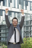 Portrait of cheerful businessman celebrating success outside office building Stock Photo