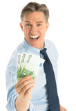 Portrait Of Cheerful Businessman Holding Euro Banknotes. Portrait of cheerful mature businessman holding euro banknotes while standing against white background Royalty Free Stock Image