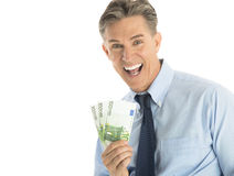 Portrait Of Cheerful Businessman Holding One Hundred Euro Bankno. Portrait of cheerful mature businessman holding one hundred euro banknotes against white Stock Photo