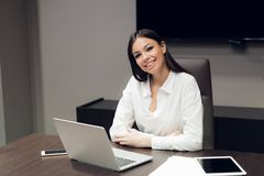 Portrait of a cheerful businesswoman sitting at the table in office and looking at camera royalty free stock photo