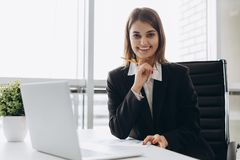 Portrait of a cheerful businesswoman sitting at the table in office and looking at camera stock photo
