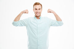 Portrait of a cheerful casual man showing his biceps Royalty Free Stock Photography