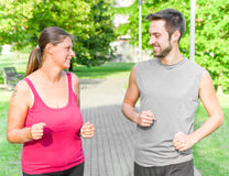 Portrait of cheerful caucasian couple running in the park Royalty Free Stock Photography