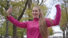 Portrait of cheerful Caucasian woman in pink sportswear talking through videochat, showing thumb up and starting running. Female runner training in the morning stock video