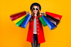 Portrait of cheerful cheery positive glad charming elegant adora. Ble curly-haired lady in eyeglasses eyewear holding colorful bags wearing jeans denim fall stock images