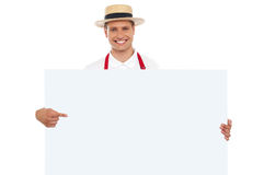 Portrait of cheerful chef pointing at placard Stock Photography