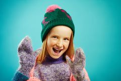Portrait of cheerful child girl wears winter mittens, warm sweater, hat with pompom and openwork cape scarf on blue royalty free stock image