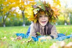 Portrait of the cheerful child in a wreath from autumn leaves Royalty Free Stock Photography