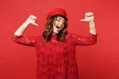 Portrait of cheerful confident young woman in lace dress cap pointing thumbs on herself isolated on bright red wall royalty free stock photography