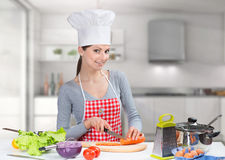 Portrait of a cheerful cooking woman in the kitchen Royalty Free Stock Photos
