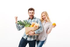 Portrait of a cheerful couple holding paper shopping bag. Full of groceries and looking at camera isolated over white background Royalty Free Stock Photos