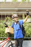 Cheerful courier with bicycle stock image