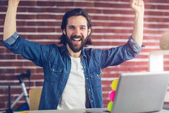 Portrait of cheerful creative businessman in office. Portrait of cheerful creative businessman with arms raised in office Stock Photos