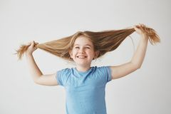 Portrait of cheerful cute little blond girl in blue t-shirt laughing with closed eyes, holding hair with hands, having Royalty Free Stock Photos
