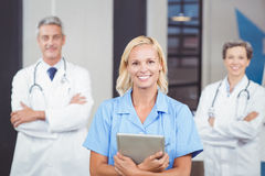 Portrait of cheerful doctor holding digital tablet while colleagues with arms crossed stock photo