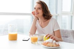 Portrait of cheerful and dreamy brunette woman holding her head. While having breakfast at the kitchen table Royalty Free Stock Image