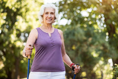 Portrait of cheerful elderly lady in green park working out Royalty Free Stock Image