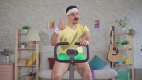 Portrait energetic man athlete from the 80`s with a mustache engaged at home on a stationary bike