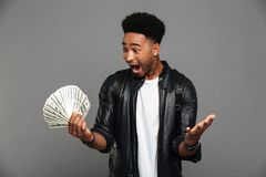 Portrait of a cheerful excited afro american man. In leather jacket holding bunch of money banknotes and celebrating isolated over gray background Stock Photography