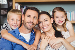 Portrait of cheerful family against shelf in living room Royalty Free Stock Photography