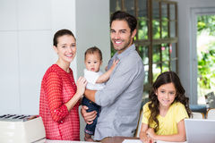 Portrait of cheerful family at desk Stock Photography