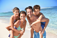 Portrait of cheerful family by the sea. Portrait of cheerful family at the beach, piggyback ride Royalty Free Stock Photo