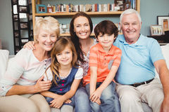 Portrait of cheerful family sitting on sofa Stock Image