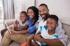 Portrait of cheerful family using digital tablet while sitting on sofa Royalty Free Stock Photography