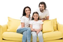 portrait of cheerful family in white shirts on yellow sofa stock images