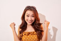 Portrait of cheerful fashion girl going crazy in a orange polka dots dress isolated on beige stock photography