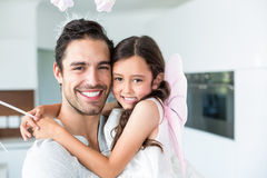Portrait of cheerful father carrying daughter in fairy costume Stock Images