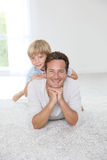 Portrait of cheerful father and his son lying on the floor Royalty Free Stock Photography