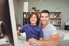 Portrait of cheerful father and son using computer Royalty Free Stock Image