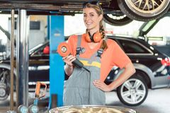 Portrait of a cheerful female auto mechanic wearing safety equipment. While holding a car polishing machine in a modern automobile repair shop stock photography