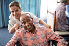 Portrait of cheerful female doctor standing with disabled senior man on wheelchair Royalty Free Stock Image