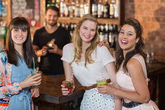 Portrait of cheerful female friends holding drinks in bar Stock Photo