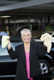 Portrait of cheerful female owner showing washcloth in car wash Royalty Free Stock Photography