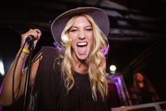 Portrait of cheerful female singer performing at nightclub. During music festival Stock Image