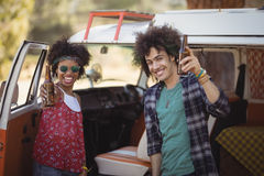 Portrait of cheerful friends holding beer bottles. While standing by van Stock Photo