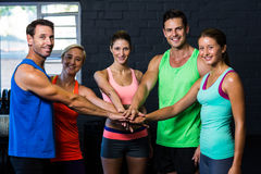 Portrait of cheerful friends putting hands together in gym Royalty Free Stock Photography