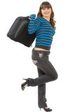 Portrait of the cheerful girl. The young girl in jeans and with a suitcase in hands royalty free stock photos