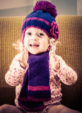 Portrait of cheerful girl clapping with a knitted cap and scarf sitting on a chair in a retro style. Stock Images