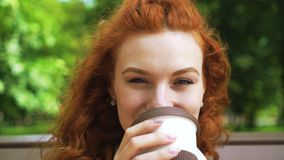 Cheerful red haired girl looking at camera and drinking coffee. Portrait of cheerful girl with curly red hair looking at camera and drinking coffee outdoors stock footage